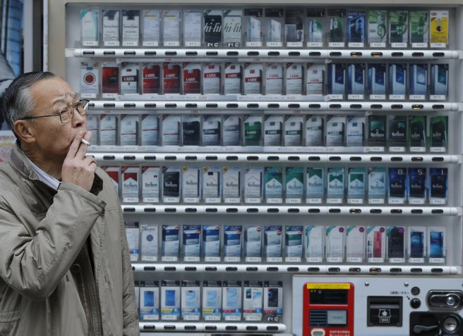 File photo of a man smoking a cigarette in front of a vending machine selling cigarettes of Japan Tobacco Inc and other cigarette companies in Tokyo