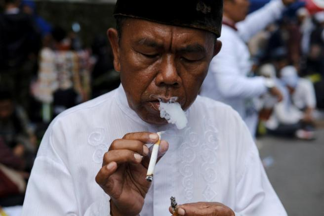 An Indonesian man smokes a cigarette during a protest near South Jakarta court in Jakarta