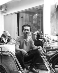 A transport worker having a cigarette break sitting in his Becak